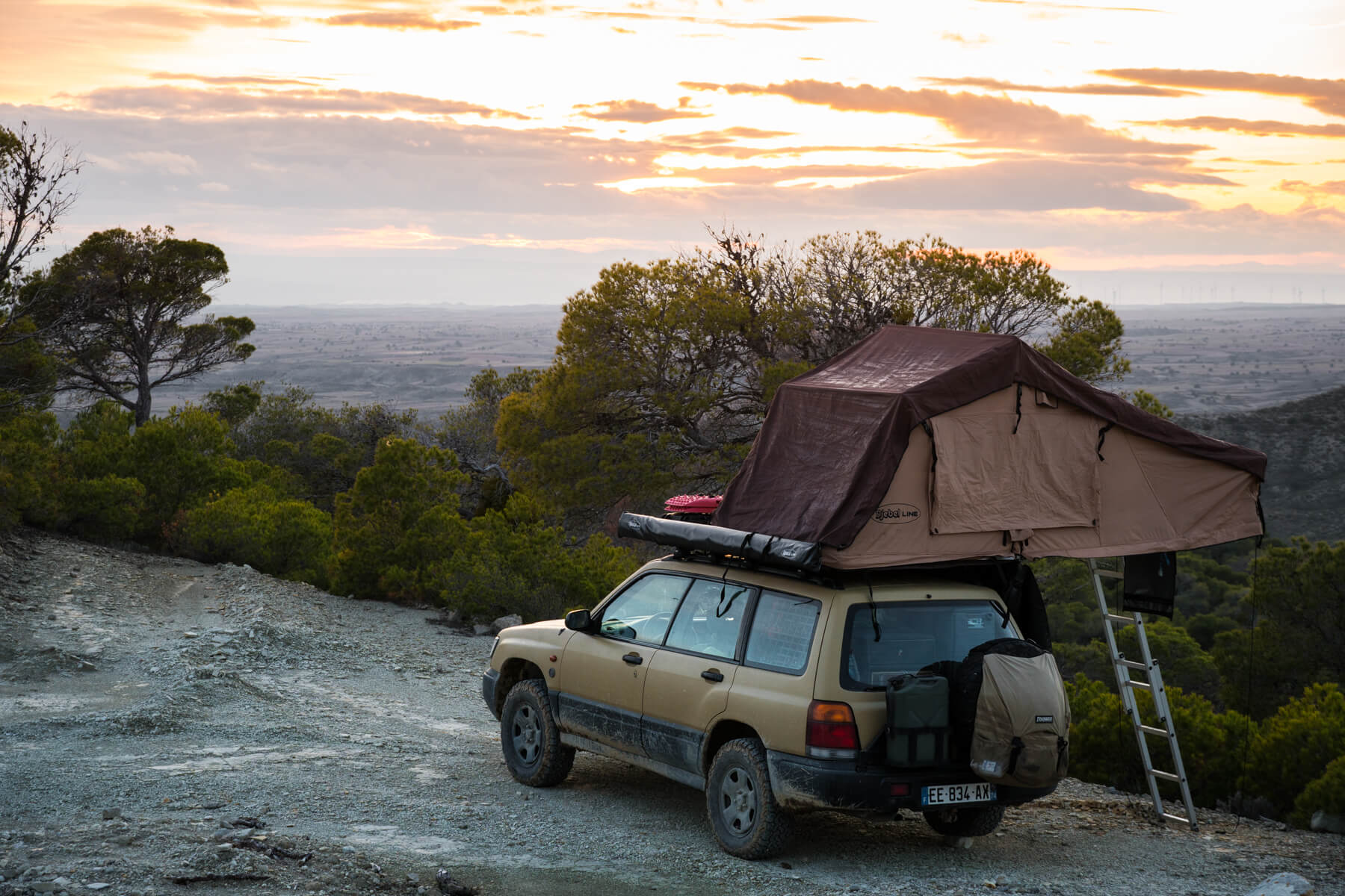 an overland subaru forester with a roof tent and a sunset